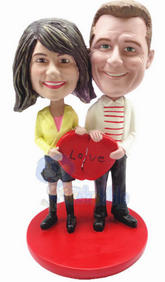 A couple standing together on a base, each holding part of a heart to makes them complete custom bobblehead doll